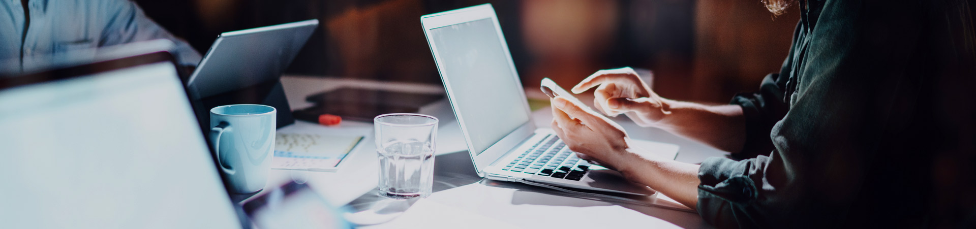 Banner image, woman working on her phone and laptop